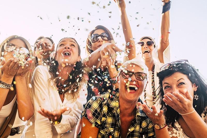 Glade mennesker på firmaudflugt med fest og glimmer.