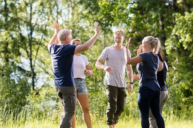Glade mennesker har det sjovt sammen på udflugt i skoven.